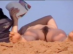 cute woman with hairy pussy sunbathing at nude beach
