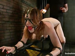 Cici Rhodes likes the dungeon. Thonged to a board, bound and gagged the brunette receives a punishment with hot wax and spanking. Her master removes a metal plug from her ass, then re-inserts it, attaching a rope from it to her head. A sex tool runs over her pussy, making her want to cum, but can't yet.