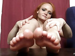 This woman actually wants to wrap her feet around a dick and make it cum, but unfortunately this babe does not have a dick handily available. Therefore, this babe is making use of the next superlatively admirable thing, which is a naughty big darksome sextoy standing up right on the table. She is caressing that with her feet.