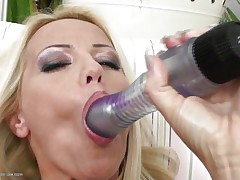 Blond milf wearing merely a pair of sexy black nylons is playing solo with her big dildo, that hottie sucks it and the fills her bald vagina with it, fucking herself as hard as that hottie can but that is not enough. Luckily her brunette girlfriend is ready to help and gives her a hand, rubbing her cunt and then fingering it, wish to see what else she's ready to do?