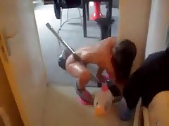 Skinny bare wife hoovering apartment wearing just a couple of pink slippers.