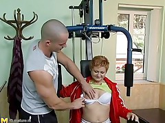 See this hawt red headed cougar who takes advantage of this young gym instructor. That babe has great sex experience and starts seducing him, like this babe well knows. This old chick has all this babe needs to make a guy happy. That babe starts taking off her clothing to turn the young chap on. This guy likes playing with her tits.